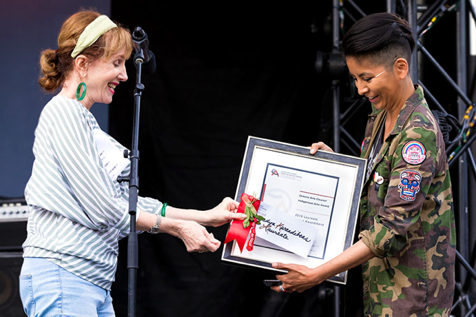 Photographer Nadya Kwandibens (right) receives the 2018 Ontario Arts Council Indigenous Arts Award from OAC Chair Rita Davies (left) during the Indigenous Arts Festival at Fort York in Toronto. (Photo: Brendan Albert)
